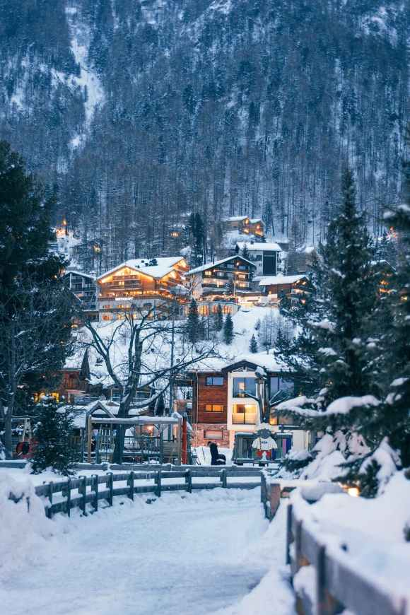 winter resort houses located on forested snowy hilly terrain