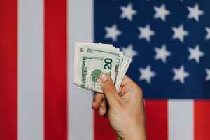 crop person showing pack of dollars against american flag