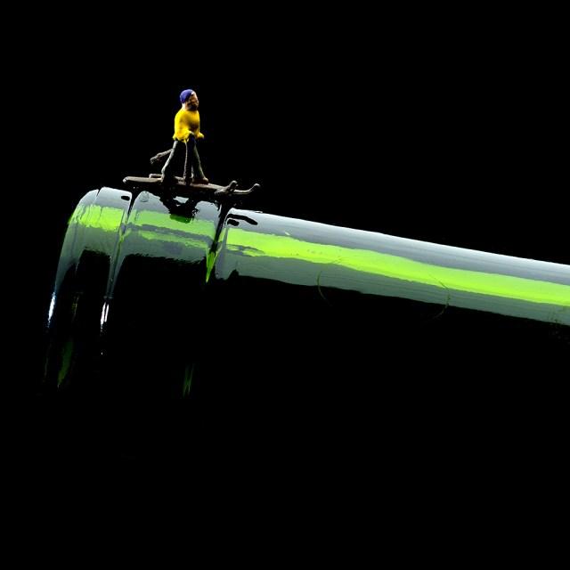 Un esquiador indoor con fondo negro esquiando el cuello de una botella vacía de vino turbio