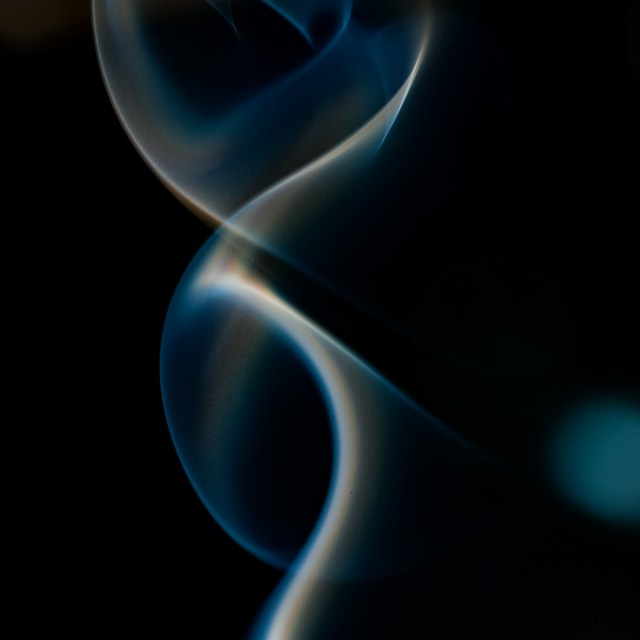 Voluta de humo sobre fondo negro con toques azules. Un doble ocho de humo