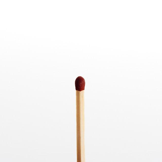 Una cerilla sobre fondo blanco esperando quemarse para algo útil