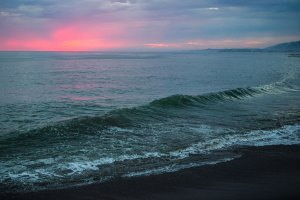 California coastline at sunset with wave in foreground