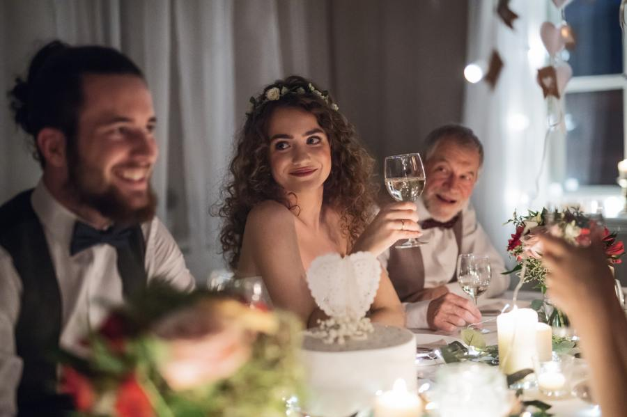 A young couple sitting at a table on a wedding, talking to guests.