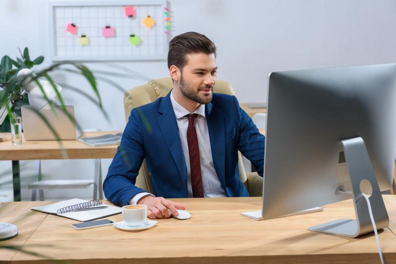 happy businessman looking at computer at working place