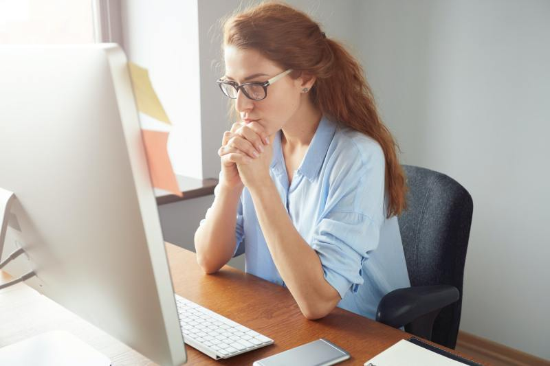 Portrait of young successful female boss reflecting on her business goals while sitting in front of