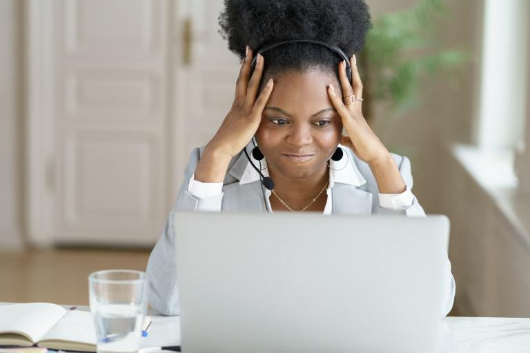 Angry annoyed afro businesswoman screaming, wear headphones talking to a bad customer work on laptop