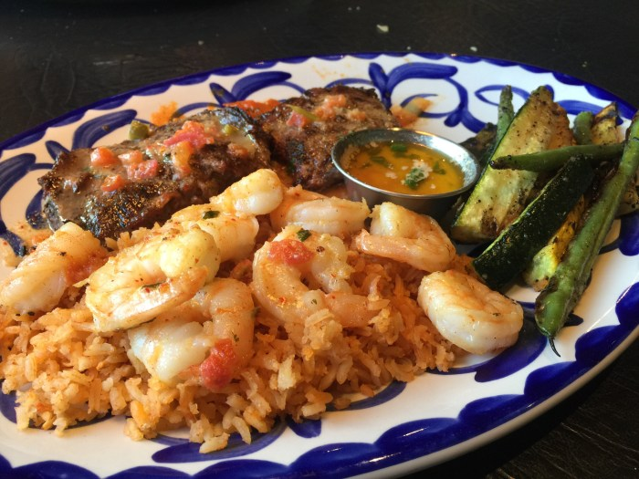 Plate of shrimps, rice and other delicious items.