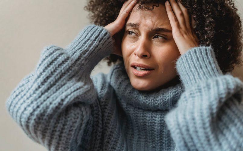 women with stroke symptoms holding her head