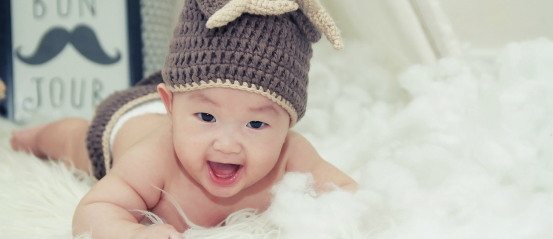 a happy chinese baby with a cute beanie on smiles atop a sheepskin rug, representing our discussion regarding chinese babies and eczema in china