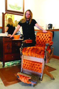 Barber Phil Mills stands at the ready with his vintage crushed-velvet chair. Photo by Molly Oleson.