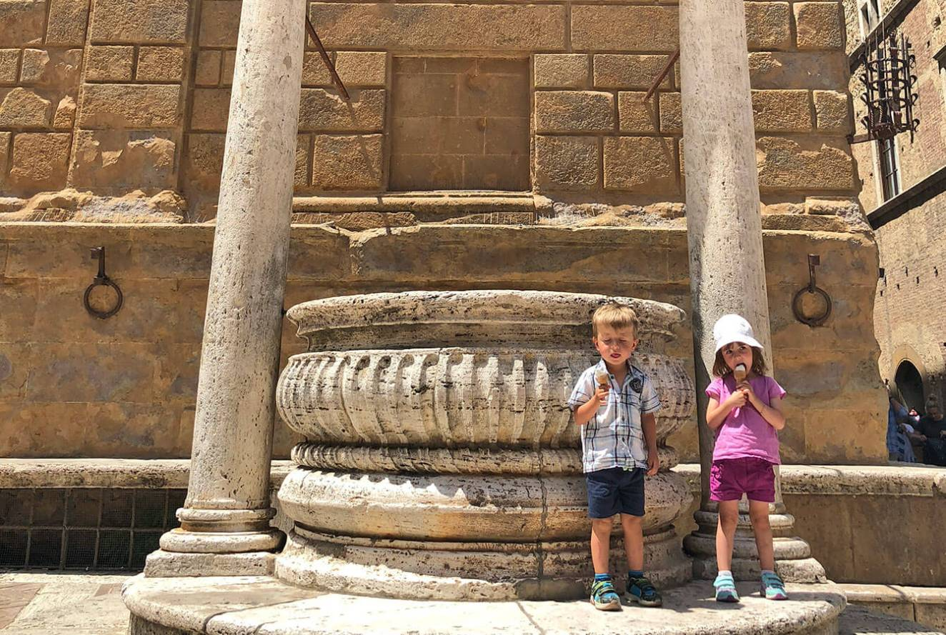 Kids standing in the Piazza Pio II center by the fountain