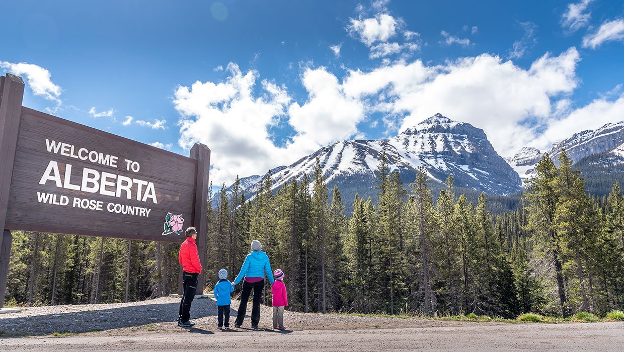family standing at the welcome Alberta signe