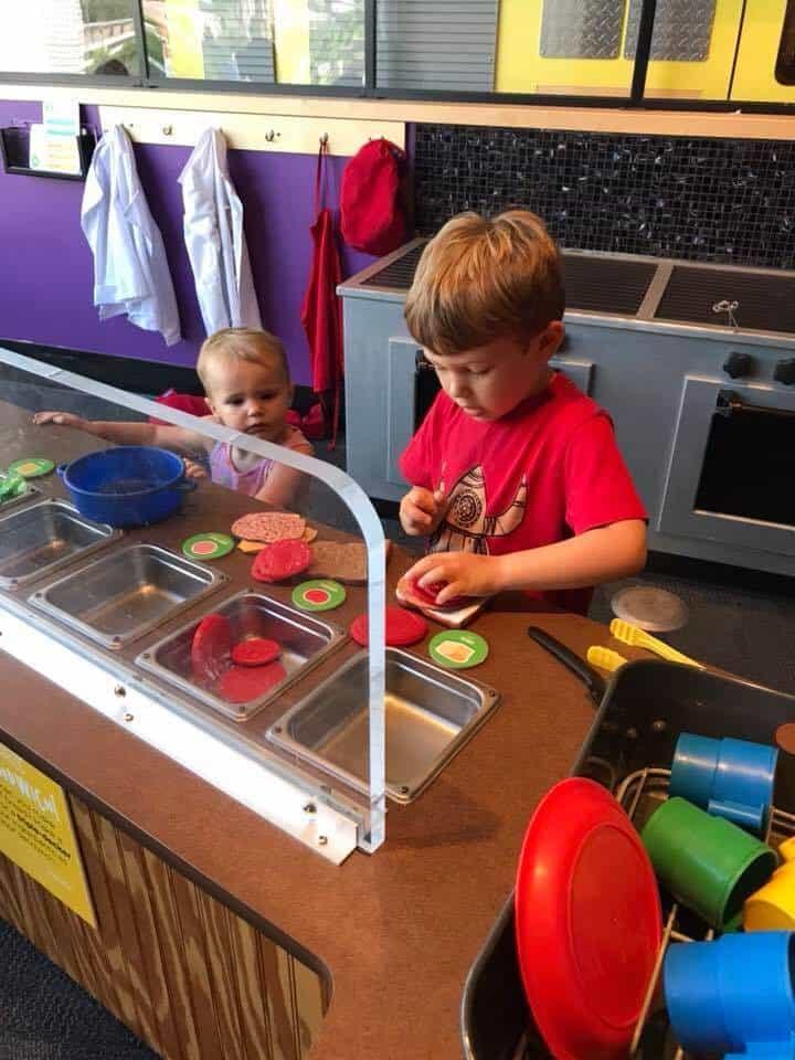 Boy making sandwiches in the play kitchen at the Glazer Children's Museum