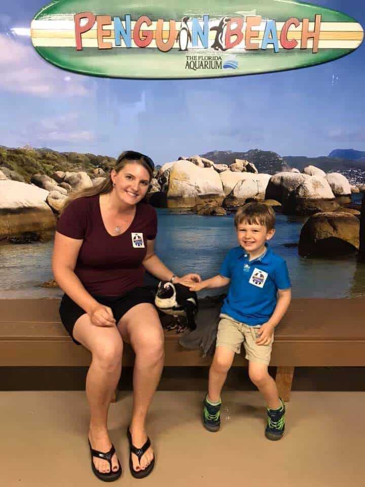 Mother and son sitting with a penguin at the Florida Aquarium