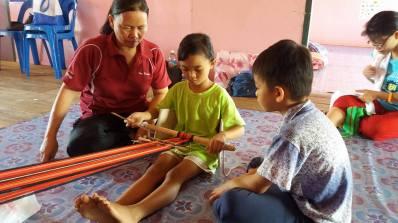 Raini teaching her nephew and niece how to 'mangavol' or weave at the Liu CLC in Pitas.