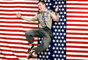 Patrick Selover jumping with flag background