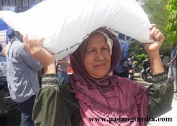 Salah seorang warga membawa Raskin yang disalurkan Pemko Padang, Rabu (20/1). (der)