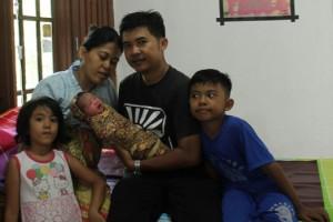 Bambang bersama sang isteri menggendong buah hati ketiganya yang lahir bertepatan dengan fenomena alam GMT, Rabu (9/3) pagi. (baim)
