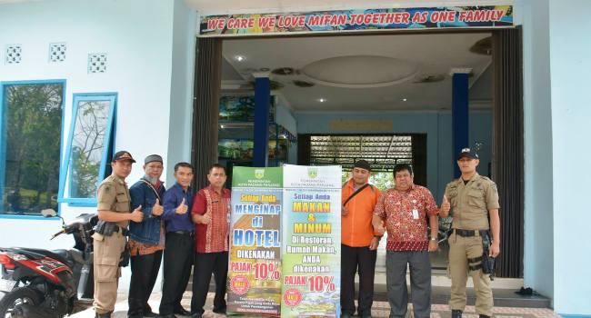 Petugas dari Pemko Padangpanjang memasang banner pajak 10 persen di sejumlah rumah makan, restoran, hotel dan tempat hiburan, Rabu (11/1). (HUMAS)