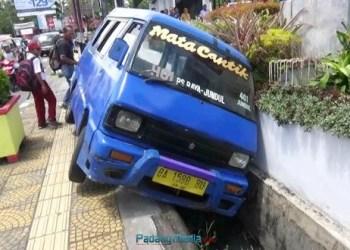 Sebuah angkot naik ke trotoar dan terperosok ke selokan setelah ditabrak dari belakang oleh mobil lain di Jalan Bagindo Aziz Chan, Padang, Selasa (26/9). (dio)