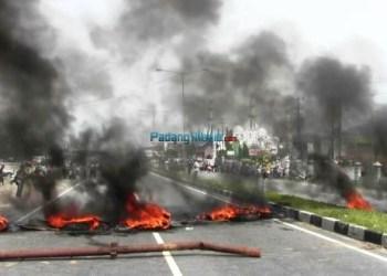 Warga Forum Nagari Tigo Sandiang menggelar aksi blokir jalan dan bakar ban sebagai kemarahan terhadap kedatangan petugas BPN yang akan melakukan pengukuran tanah di kawasan By Pass, Jumat (25/1). (feb)