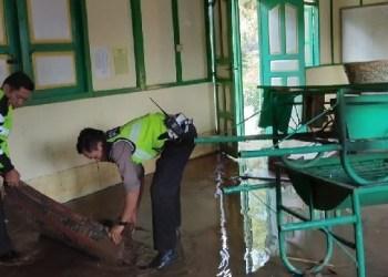 Petugas membersihkan banjir bandang yang masuk hingga ke musala. (foto; ist)