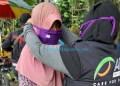 Ketua MRI ACT Deli Serdang, Pristia Wati sedang memasang masker kepada seorang ibu yang sedang berada di seputaran Lapangan Merdeka Medan.