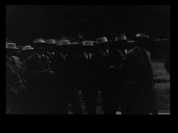 Black and white image of men in suits and straw hats.