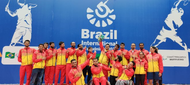 Players are dressed in yellow and red athletic attire. The group is posing in front of a giant blue poster of the Brazil International competition.