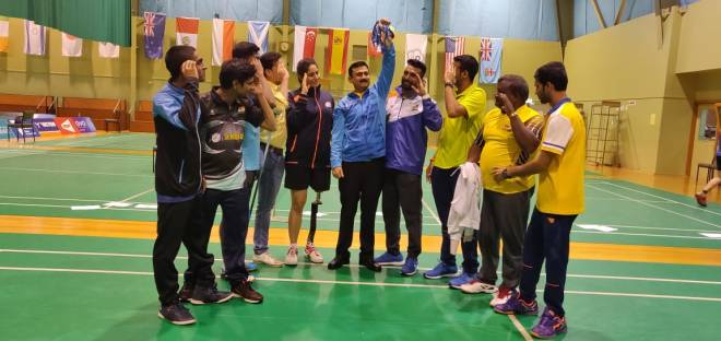 Image of Khanna holding medals up in a bunch and disabled players are seen saluting towards him (and the medals)