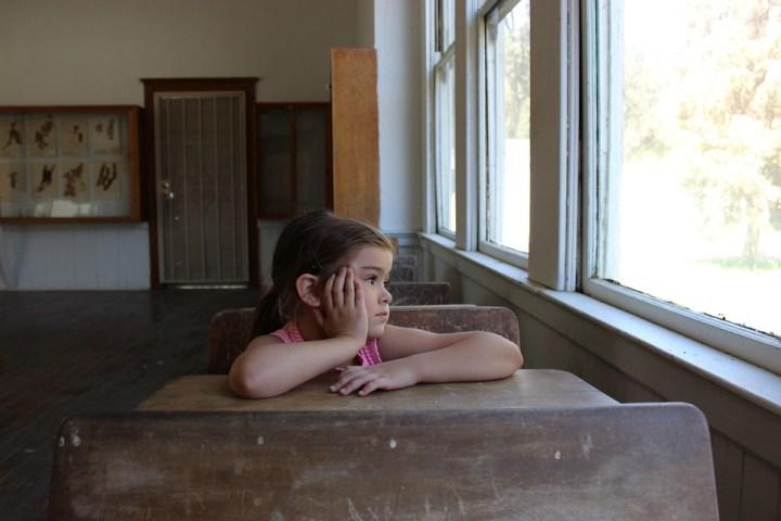 Kind, allein, sieht aus dem Fenster