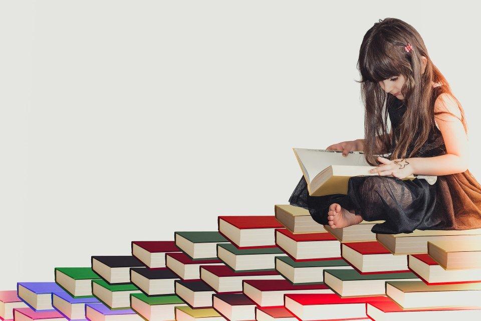 Kind auf einem Stapel Bücher