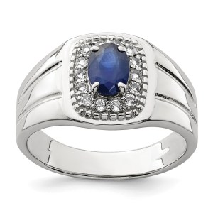 Men's sterling silver ring with a prong set, oval blue sapphire that measures 5.18 mm X 7 mm and weighs 1.34 ctw and is surrounded by sixteen, prong set, round white topaz stones. This ring has textured sides and a polished finish.
