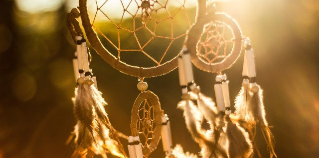large dreamcatcher, backlit by sunlight on the horizon, with smaller dream catchers at the sides and bottom, and feathers and beads hanging from each