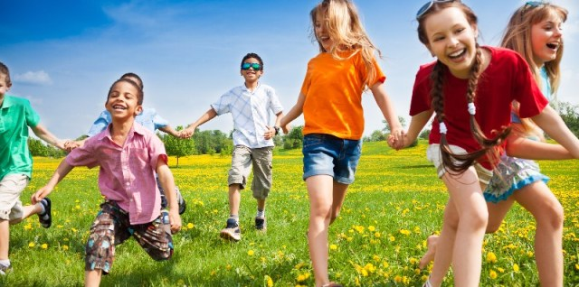 children holding hands running through a grassy field