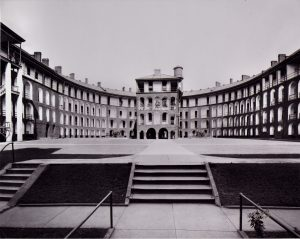 Large prison courtyard with a guard tower in the middle of the frame flanked by four stories of cells stretching a width of ten cells across the image