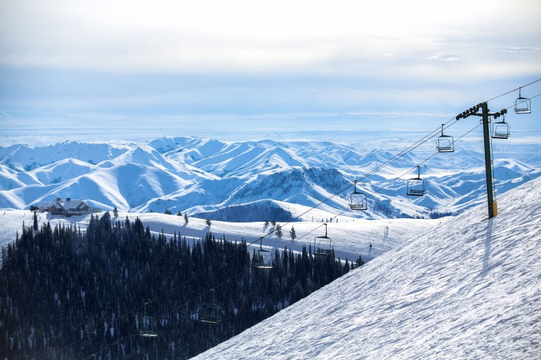 A chairlift going up a ski mountain.