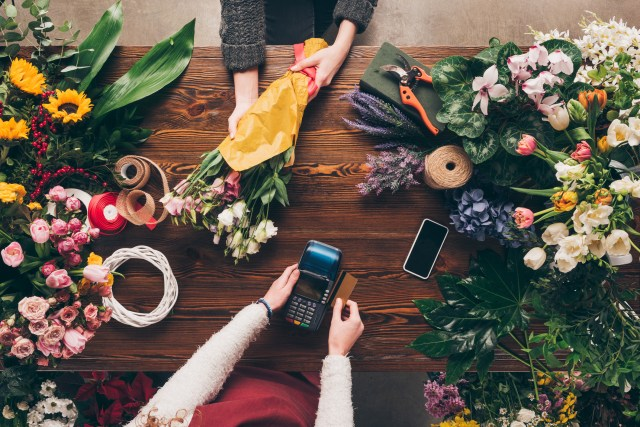 A credit card being swiped at a florist shop.