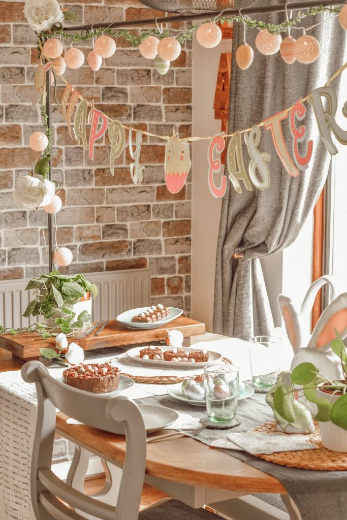 image of a table decorated with an easter theme including happy easter bunting and crockery serving chocolate treats