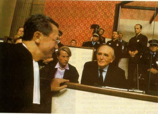 Photo couleur de Ma�tre Verg�s se penchant vers Klaus Barbie, dans le box des accus�s.