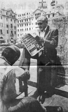 Photo de Klaus Barbie sur une place, il lit le journal tandis qu'on lui cire les chaussures