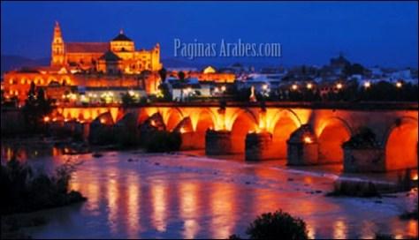 Córdoba, bañada por el río Guadalquivir, al anochecer, con la Mezquita y la catedral al fondo.