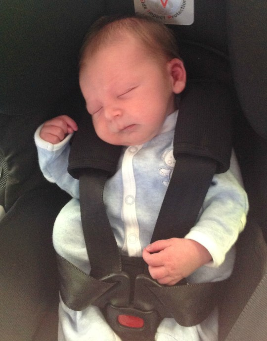 Asleep in his car seat.
