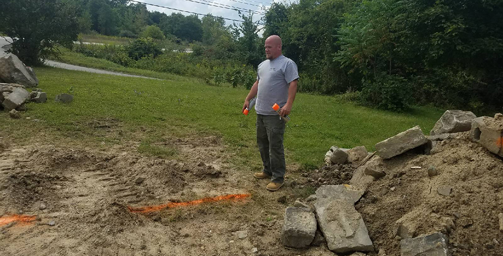 Brother Brian Seeger, contractor, marks the outline for the new house's foundation.