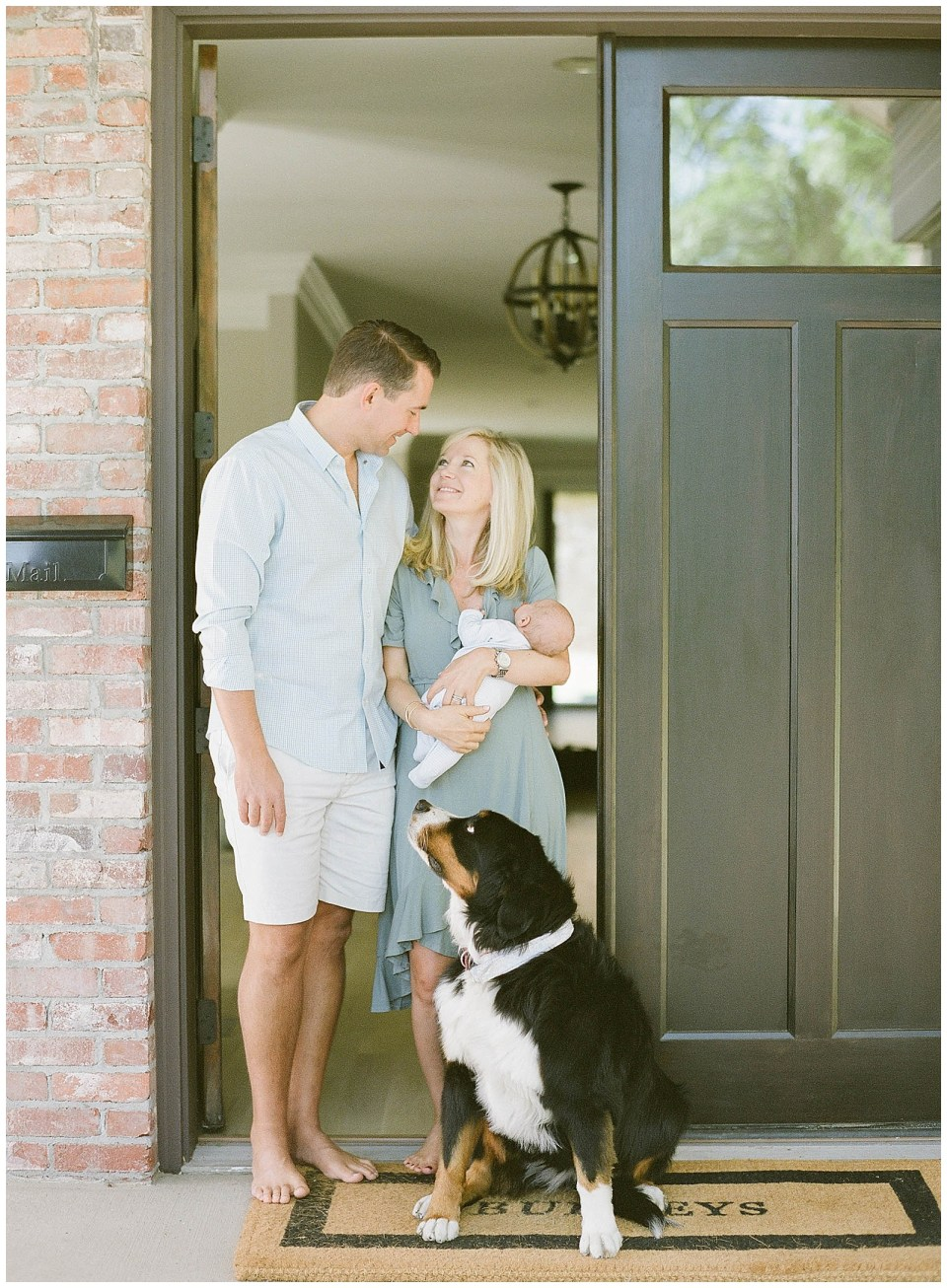 Denver family photographer - family holding new baby outside front door with dog portraits