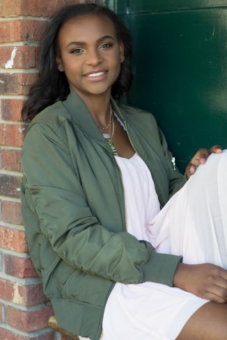 girl leaning against a green garage door for senior pictures