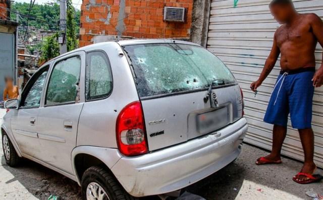 Morador observa carro atingido por tiros em tiroteio no Alemão (Foto: Bruno Itan/Arquivo Pessoal)