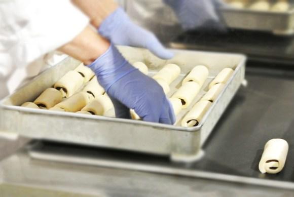 クロワッサンショコラを鉄板に敷き詰めるプラビダのパン職人