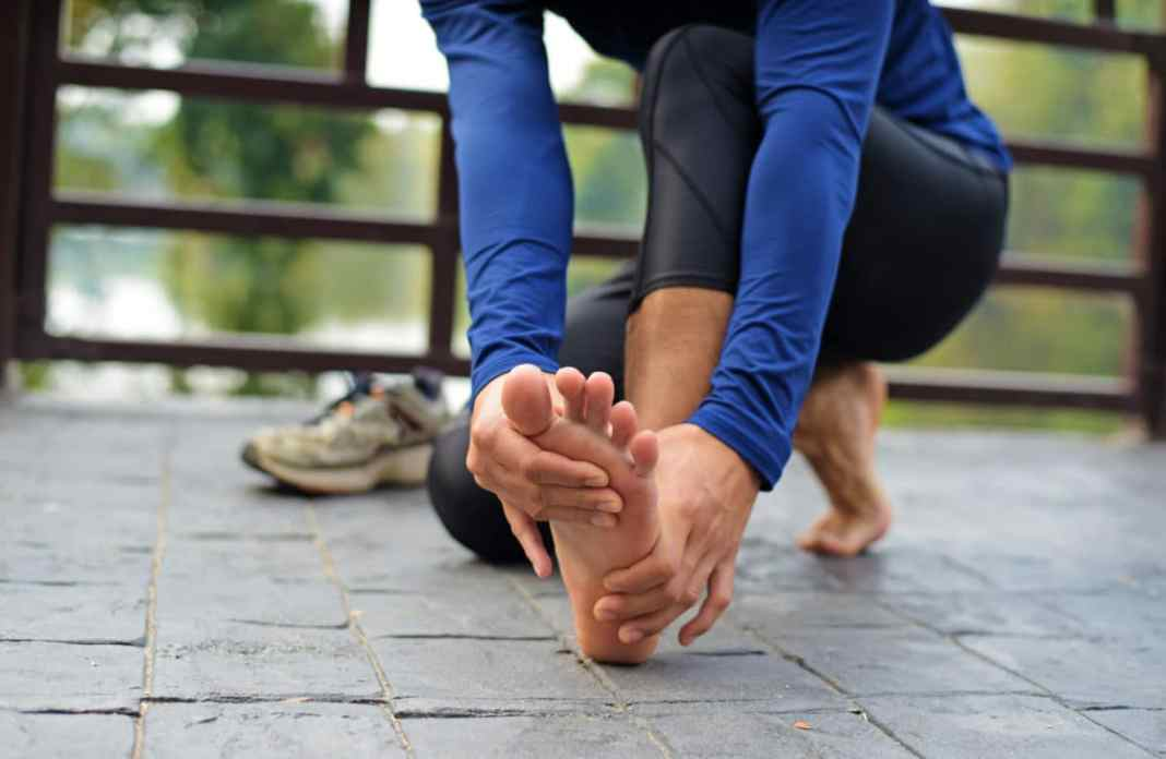 runner holding her foot with stress fracture