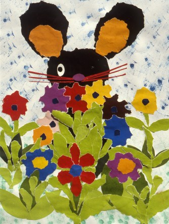 Picture of rabbit in a garden peeking over the flowers